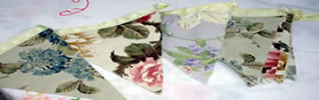 A collection of vintage linen table cloths and vintage floral bunting
